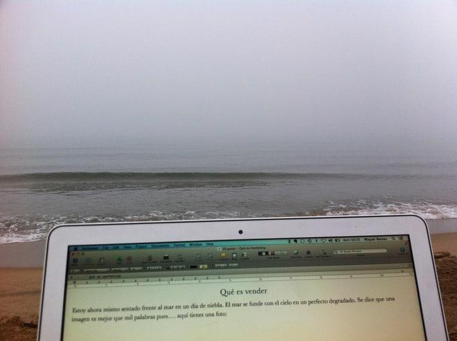 ordaenador escribiendo vista al mar nublado
